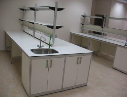 שולחן מעבדה כולל כיור נירוסטה ברזים, מדפים, ארון ושקעים.