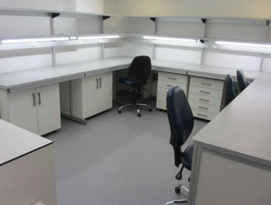 שולחנות מעבדה בהיקף החדר כולל 2 מדפים ותאורה.