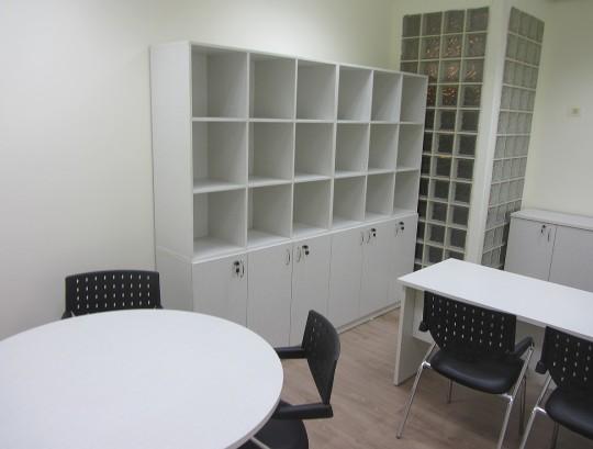 חדר מנהל הכולל שולחן ארגונומי, שולחן עגול לפגישות, ארונות וכוורות לאחסון.