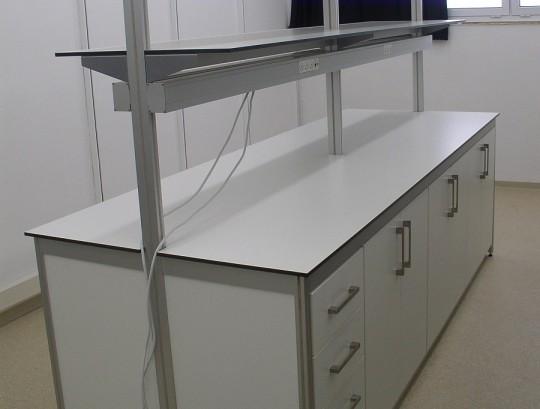 שולחן מעבדה דו צדדי כולל מדפים, HPL, תעלת חשמל עם שקעים וארונות אחסון.