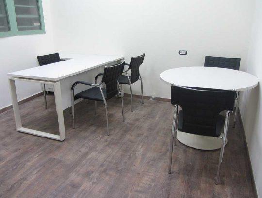 """חדר מנהל כולל שולחן בצורת """"ר"""", שולחן עגול וכסאות אורח."""
