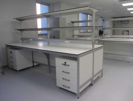 """שולחן מעבדה דו צדדי כולל משטח HPL  בעובי 12 מ""""מ כולל מדפים, תעלות חשמל וריהוט."""