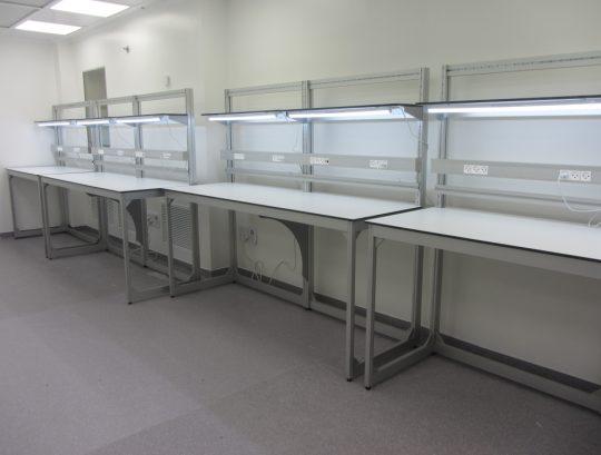 שולחן מעבדה משטח HPL כולל מדפים ניתנים לניוד ופרופיל אלומיניום לתליית ארקליות.