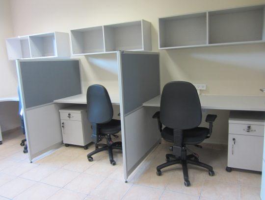 עמדות עבודה בהיקף החדר כולל מחיצות משטחים צפים וארונית אישית לכל נציג
