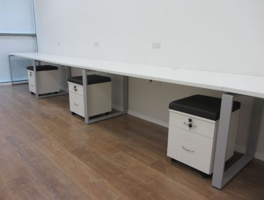 משטחי שולחן בהיקף החדר כולל רגלי חלון וארגזי מגירה עם כריות לישיבה