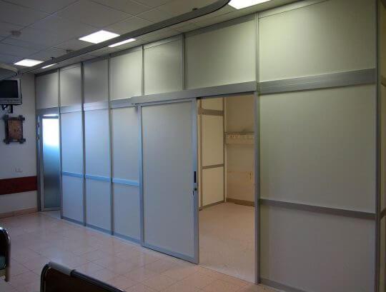 מחיצות רצפה תקרה לסגירת אזור רופאים במילוי HPL כולל דלתות הזזה ודלתות ציר.